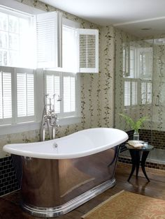 The climbing vines in this Connecticut bath look like wallpaper but are Ann Sacks tile. The tub is from Lefroy Brooks.