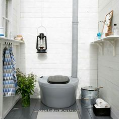 Composting toilet in a blue and grey summer cottage bathroom.