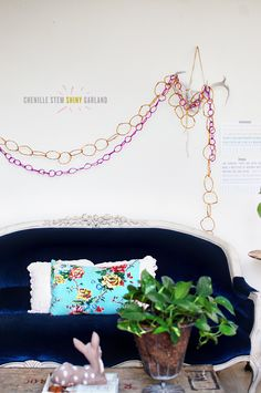 DIY: chenille stem shiny garland.  It's a variation on the traditional paper chain.  I like the airy look.