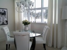 Dining room. Round table. Glass top. White chairs.