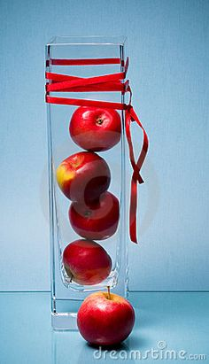 Stacked fruit in tall glass vase wrapped with ribbon