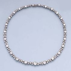 A DIAMOND NECKLACE  The graduated line of circular-cut diamonds alternating with geometric patterns of five smaller diamonds, millegrain setting, circa 1930, with maker's mark GK for Ets. Krakenbuhl and French assay mark for gold