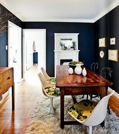 Dark walls work in this room, along with a cozy rug and modern chairs. Love the mash up.