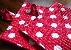 cool potholders...cool contrast between round dots and concentric squares quilted