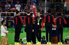 Lauren Hernandez (C) of the United States waves to fans on the podium at the medal ceremony for the Artistic Gymnastics Women's Team Final on Day 4 of the Rio 2016 Olympic Games at the Rio Olympic Arena on August 9, 2016 in Rio de Janeiro, Brazil.