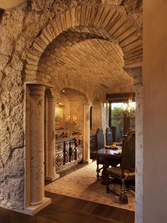 This stone archway provides a memorable entrance into this Italian-style dining room. The shape of the entryway, the classic style of the dining table and the marble pillars channel Tuscan style.