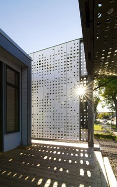 this is just a lovely idea..a photograph of sunlight through the trees was enlarged to total pixelation and that pattern was used to creat the screen on the porch of this building..