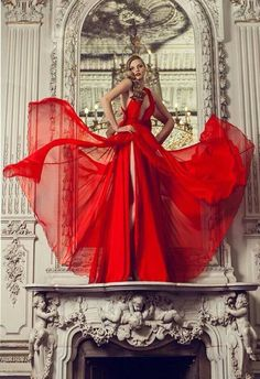 "Shot in an Italian interior featuring columns and intricate wall details, the flowy red gown exemplifies the famous shade of ""Valentino Red"", which the designer is famous for."