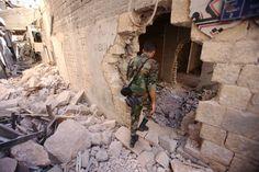 A Syrian soldier walks through the war-damaged al-Farafira souk in Aleppo's historic city centre on September 16, 2016 (AFP Photo/Youssef Karwashan)