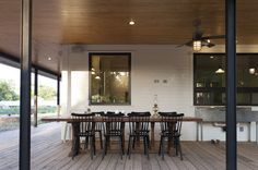 Instead of having an indoor dining room, which would have shrunk the kitchen, the homeowners put their dining room on the porch. Cedar planks make up the porch flooring. Rauser chose not to treat the wood, because he wanted it to be a living element that changes over time, displaying scratches and discoloration to give it an older, worn look.