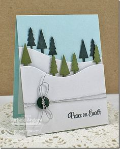 winter scene card with snow banks and green trees, and ribbon and button embellishment
