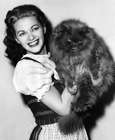 Actress Yvonne de Carlo (pretty!). I don't know who she is, but MAN is that an excellent cat! I may not know who she is, but she sure isn't afraid of cats! <3 ). I love everything about this photo.