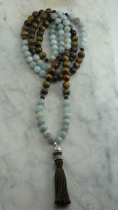 The Patches of Blue Mala is made from 108 aquamarine and tiger eye mala beads. It is completed with a Tibetan lotus guru. Buddhist prayer beads for calming.