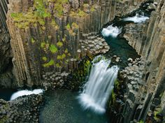 See a photo of a waterfall flowing through columns formed by ancient lava flow in Iceland, from National Geographic.