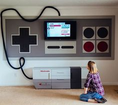 Thanks to some creative woodworking and a clever paint job, Indiana mom Rorie Lizenby has transformed a bland playroom into a larger than life Nintendo-themed game room for her two sons. The project, which included modifying an entertainment center to look like a NES console, took this high school chemistry teacher two weeks to complete and has received endless praise on Reddit. #Nintendo #NES #Gaming