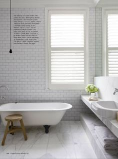 claw foot tub white subway tiles entire bathroom wall