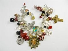 Blessed Mother ornate pendant, crosses , saint holy medals, red black and gold colored beads hang from a religious silver plated chain link bracelet  The holy medal are as follows;  St Benedict Medugorje Archangel Michael Madonna Virgin Mary Lady of Guadalupe St Juan Diego  All together are 20 charms including the handmade ones.  The Virgin Mary ornate bronze pendant charm holds a 13 x 18 mm colorful laser printed image and is protected by a domed glass oval glass tile.  There are gold…