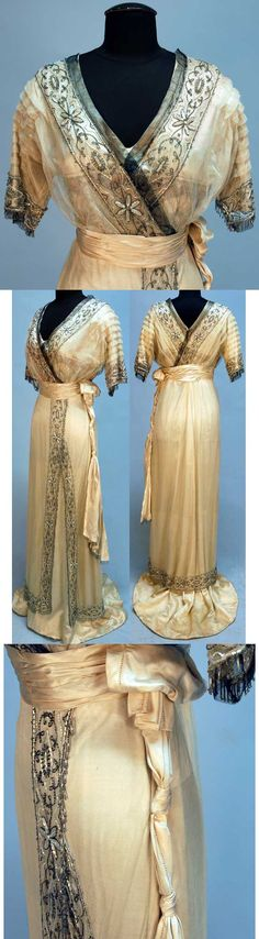 Evening gown, ca. 1911. Ivory satin beneath cream net. Short, pleated sleeves and V-neck are decorated with bands of crystal and opalescent white beads in a pattern of daisies, with a beaded fringe. The satin bodice has a band of printed silk and metallic net. Satin cummerbund with side drape, net overskirt with off-center slit above trained silk skirt.