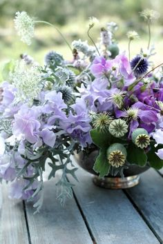 sweet peas, dusty miller, clematis, globe thistle, queen anne's, sage, geranium and poppy pods | Purple Floral Arrangement