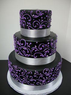 Black cake with purple swirls and silver ribbon