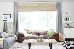 Like the natural shades and gray/blue curtains.  Brown leather sofa, cream rug, black and white pictures.