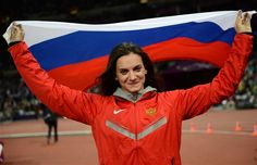 Russia's Yelena Isinbayeva waves her national flag as she celebrates winning the bronze medal in the women's pole vault final at the athletics event of the London 2012 Olympic Games on August 6, 2012 in London.