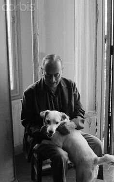 The polish writer Witold Gombrowicz smiles while petting his dog.