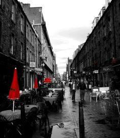 Función estética y artística: prentende adornar el entorno utilizando elementos del lenguaje plástico visual, en este caso, las sombrillas en rojo, las mesas limpias y ordenadas, las personas que pasan por esa calle.