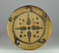 Etruscan Genucilia plate, 4th century B.C.  Etruscan Genucilia plate,decorated with a four pointed star on the shallow floor and dots in the interstices, the narrow bulged rim enhanced with five spiral waves, 13.5 cm diameter. Private collection