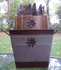 "Metal Flower - Set of 8    Package includes 8 natural burlap pouches embellished with a metal flower.  Pouches are 6"" X 3 3/8"" - custom sized to hold a napkin and set of silverware."
