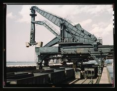 Unloading a lake freighter at the Pennsylvania Railroad iron ore docks by means of Hulett unloaders, Cleveland, Ohio. In the foreground, empty cars are waiting to pass under the unloaders to pick up their loads