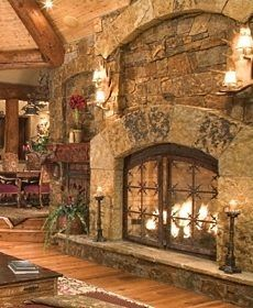 cozy and rustic fireplace design inspiration.  Love the different rocks being used, the antler sconces, although I wonder if I would miss having a mantle