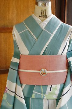 白の地に、グラデーションも美しい水浅葱色の縞と、薊模様が染め出されたツモリチサトの浴衣です。