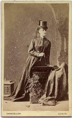 Late 1870's riding habit. Note how much plainer the bodice is and less full (but still very long) the skirt is compared to the photograph of the 1860's habit. The bodices of the habits, became more severe and masculine looking during the mid 1870's, mirroring the tight fitting basque bodices of day dress (note how the shoulder seam isn't dropped but at the natural point) but the masculinity is offset by the veil tied around and trailing from the top hat, elegant!  (From the collection of…