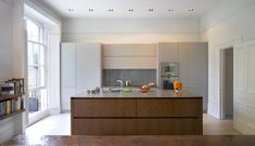 Roundhouse Urbo matt lacquer kitchen in Farrow & Ball Manor House Grey and book-matched Walnut veneer.
