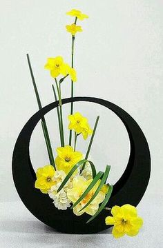 Vertical arrangement that makes a sort of L shape with Daffodils. The container for the arrangement is a modern type of container.