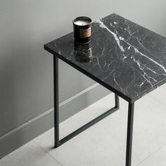 Materials: Stone top: Polished marble (nero marquina) Marble edge: Polished top and sides with the edges 1mm beveled at 45 degrees Table base: