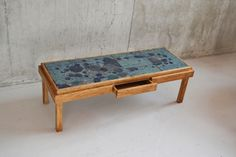 A very attractive coffee table, with illustrated ceramic tiled top. Unusually this table has a drawer in the middle. One of the tiles is cracked, and has been regaled into place. The price reflects this.  Designer: Unknown Manufacturer: Unknown Material: Ceramic tile and wood Country of origin: Belgium Size: Width 130, depth 50, height 41 cm Date: 1970's Condition: Very good vintage condition. Very minor signs of wear consistent with age and use.  NOTE: 1 tile is  repaired.