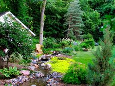 On Vacation at Home ~ This backyard renovation included the installation of a 100-foot stream down one side of the property and landscaping meant to give the feeling of a woodland escape.