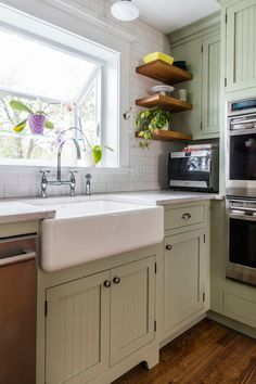 Light green paint on the kitchen cabinets blends well with the craftsman style