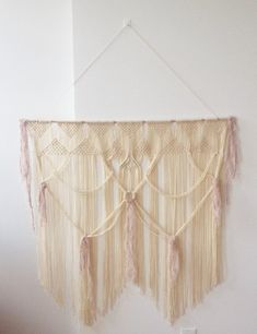 Natural and whimsical macrame wall hanging; has a dreamcatcher quality. Handmade with wool yarn in an ivory color with grey and mauve accents.
