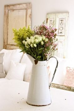 antique white pitcher holding beautiful flowers