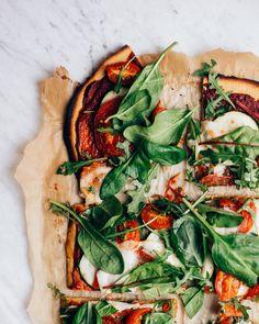 Super easy gf pizza crust with chickpea flour + tomato paste, fresh tomatoes, zucchini, greens, and bufala mozzarella on top.