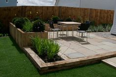New oak sleepers and sandstone paving combine to provide a stylish garden for this new Kent home.