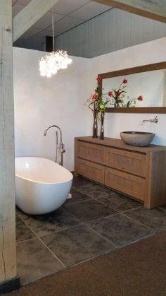 Eiken houten badmeubel met natuurstenen opzet waskom, vrijstaand bad met Dornbracht logic kranen. Rondom met eiken gebinten.
