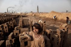 December 28, 2011 Pakistani girl Shaheen Akram stands between the bricks where she works with her family in a brick factory on the outskirts of Islamabad, Pakistan.  Muhammed Muheisen/AP