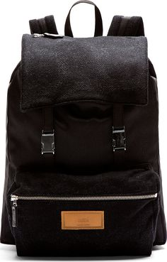 "Ami Black Wool Panel Backpack $450 USD Silver-tone hardware. Grab handle at top of bag. Adjustable shoulder straps. Foldover flap at main compartment with press-release buckle closure and zip pocket at face. Zippered compartment at front face with leather logo patch detail. Tonal wool panelling at foldover flap, front compartment, and shoulder straps. Drawstring closure at bag throat. Padded laptop compartment inside. Tonal stitching. 13""L x 18""H x 4""W. Polyester, wool, cotton. Made in…"