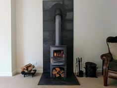 A blue Charnwood C 6 wood stove with a contemporary fireplace consisting of a natural slate tiled hearth and backing surround. The new stainless steel insulated chimney system is installed at 45 degrees through the external wall. Wood Burning Stove Corner, Wood Stove Wall, Wood Stove Chimney, Wood Stove Surround, Modern Wood Burning Stoves, Wood Stove Hearth, Granite Hearth, Wood Burner Fireplace, Hearth Tiles