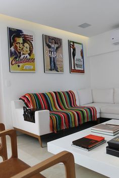 Cool creative, small living room with multicoloured striped throw rug and vintage movie posters on the wall. By Julia Queima Arquitetura