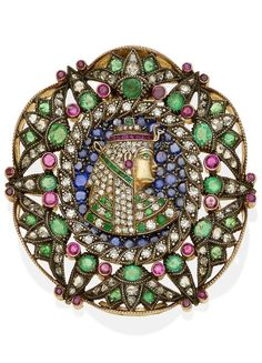 An Egyptian revival diamond, gem-set and silver-topped gold pendant set with round emeralds, rubies and sapphires, length: 2 1/4in.